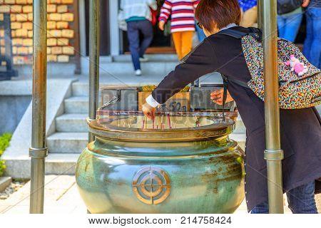 Kamakura, Japan - April 23, 2017: Japanese woman lights up at incense stick burning inside giant bronze incense burner, worshiping goddess Kannon. Hase-dera Temple is popular landmark in Kamakura.