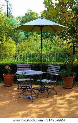 Outdoor patio furniture including a table, chairs, and an umbrella surrounded by plants and trees taken at a garden in a residential yard