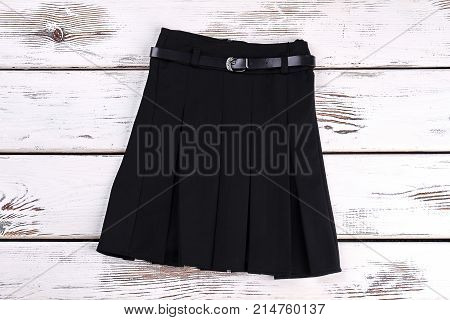 Pleated black uniform skirt. Black cotton belted skirt with pleats on white wooden background. Girls new school skirt.