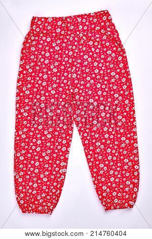 Baby-girl patterned pants, front view. Toddler girl red harems with a pattern of small white flowers, vertical image.