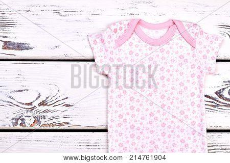 Infant girl soft cotton bodysuit. Natural short sleeve bodysuit for infant girl on old wooden background.