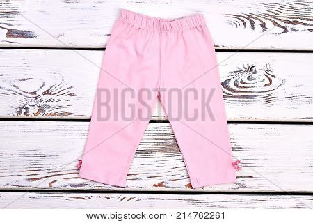 Toddler girl pink stretch capri. Beautiful light pink cotton pants for infant girl, white wooden background. New kids outfit.