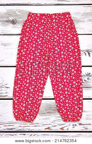 Infant girl red patterned trousers. Little girl red summer trousers in floral print, old wooden background. Kids summer apparel on sale. Baby harem pants.