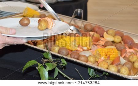 buffet line with low country boil on silver platter