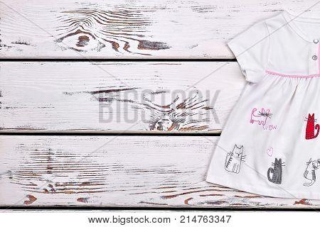 Baby girl cats cartoon dress. Newborn girl short sleeve white dress on white wooden background, copy space.