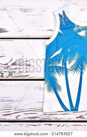 Kids beautiful printed cotton top. Childrens top quality printed t-shirt on white wooden background, top view.