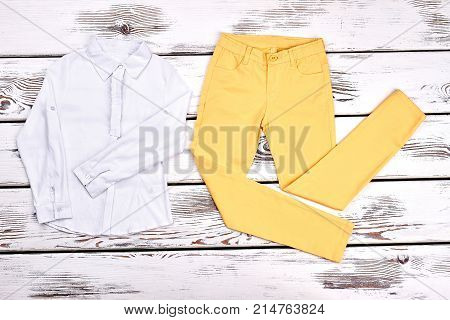 Girls blouse and yellow trousers. Teen girl white cotton shirt, colored pants on white wooden background. Young lady boutique apparel.