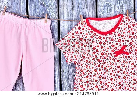 Kids clean apparel on clothesline. Infant girl fresh trousers and dress drying on rope on grey wooden background. Kids apparel in laundry.