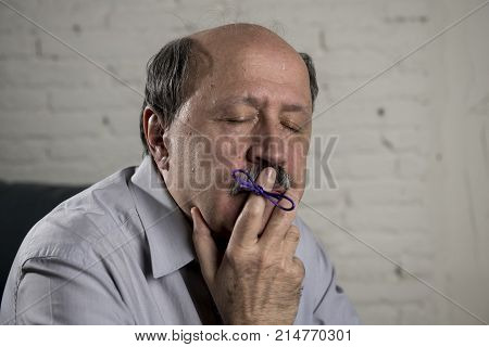 portrait of senior mature old man on his 60s at home couch alone feeling sad and worried suffering alzheimer disease holding ribbon in his finger in mental disease confusion and aging concept