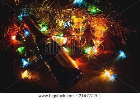 Two Glasses With Champagne And Bottle On A Wooden Table Decorated