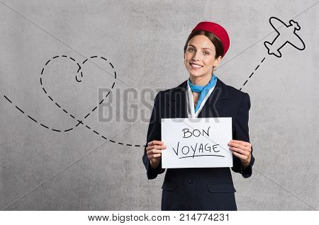 Young air hostess holding Bon Voyage sign isolated on grey background. Flight assistant holding sign with airplane route in the background. Woman stewardess with board and copy space.