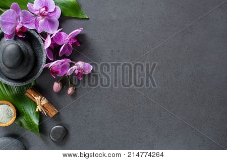 Top view of hot stones setting for massage treatment on blackboard with copy space. High angle view of orchids on green leaf with black stones pile for spa therapy. Elegant and luxury spa.