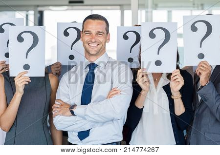 Happy businessman standing out of the crowd. Smiling business man standing with crossed arms while team hiding their faces with question mark sign. Business man find his own career path.