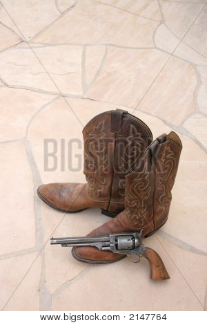 Cowboy Boots And Gun On Flagstone