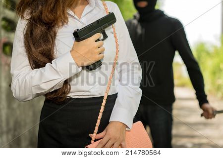 Office woman hiding gun safety self from robber thief mask danger with knife for stop gangster on street