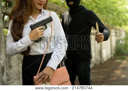 Office woman hiding gun safety self from robber thief mask danger for stop gangster on street