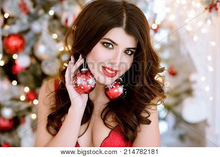 Beautiful brunette sexy Santa Clause in elegant earrings and bra. Fashion portrait of model girl indoors with Christmas tree. Cute woman in lace red lingerie with makeup. Closeup female face