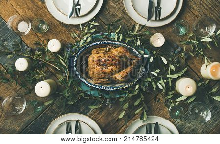 Flat-lay of holiday table setting for party, friends gathering or family celebration with oven roast chicken, plates, silverware, candles and olive branch decoration over rustic wooden table background, top view. Christmas, New year or Thanksgiving dinner