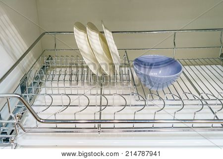 Open white dish draining closet with white dishes drying of ceramic plates and bowls fragile objects drying inside on metal dish rack