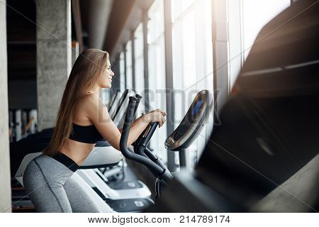 Portrait of beautiful female gym attendee running on elliptical cross trainer early in the morning. Workout before everyday job.