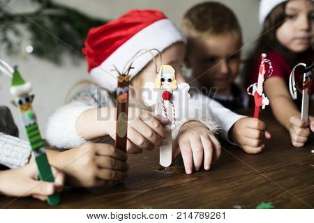 Little kids holding Christmas character decorated popsicle sticks