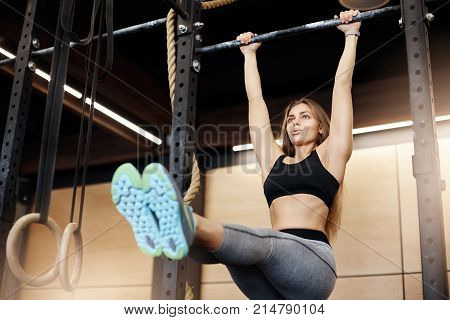 Portrait of female body fitness icon making pull ups with straight legs warming up her abs and spinal muscles looking hapy with her extremely fit body.