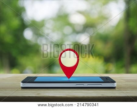 Map pin location button on modern smart phone screen on wooden table over blur green tree in park Map pointer navigation concept
