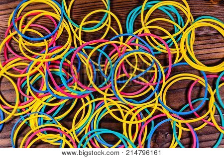 Multicolored Rubber Bands On Wooden Table. Top View