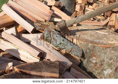 Old axe standing against a piled pieces of firewood. Axe stuck in a stump. Preparing firewood. Chopping wood for fuel