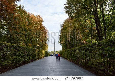 People walk along the green avenue of bushes and trees. Kiev. Ukraine.