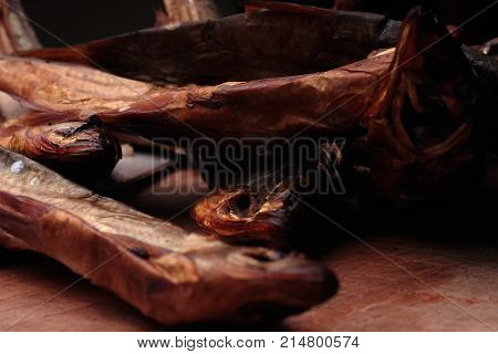 Dried fishes with no eyes laying on a wooden board