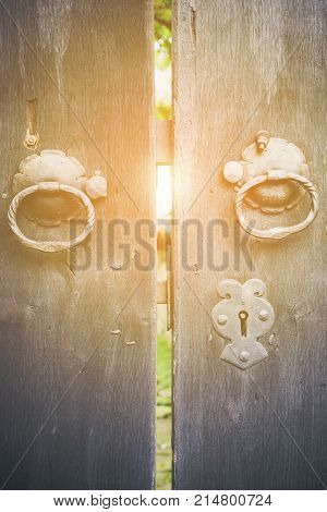Two old iron ring handles and lock on an old weathered wooden door standing ajar showing a glimpse of a garden with the sun glow in the center
