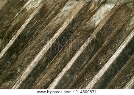 background texture: old darkened wooden wall made of overlapped diagonal slats
