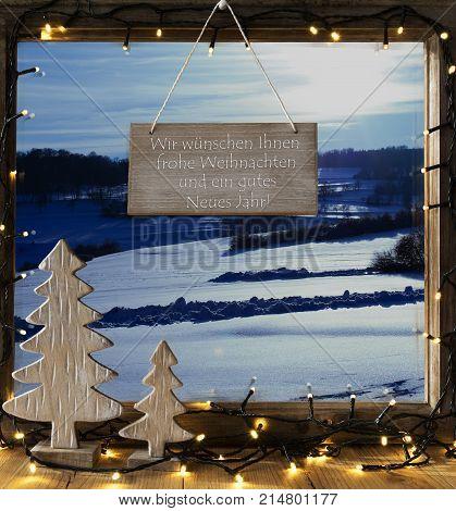 Sign With German Text Wir Wuenschen Ihnen Frohe Weihnachten Und ein Gutes Neue Jahr Means We Wish You A Merry Christmas And A Happy New Year. Window Frame With Winter Landscape, Tree And Fairy Lights.