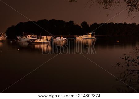 Small boats with cabins in a marina in front of an island at night