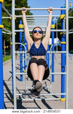 Young athletic woman trainer in a bright blue sport bra, black leggings and dark sunglasses making exercises with horizontal bar on the sport playground. Photo of girl with a beautiful sports body