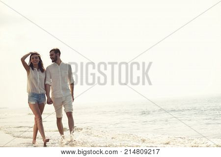 Beach summer vacation couple running on holidays. Happy fun beach vacations couple walking together laughing having fun on travel destination. Playful interracial couple in swimwear holding hands.