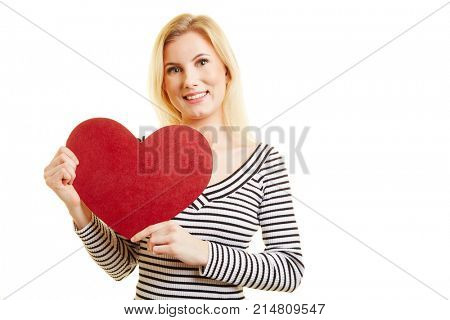 Young blond woman holds a big red heart for Valentine's Day