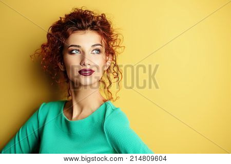 Portrait of a beautiful young woman with curly foxy hair wearing blue dress over yellow background.  Beauty, fashion concept. Make-up and cosmetics. Studio shot.