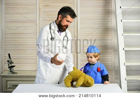 Man with beard and boy hold syringe on wooden background. Father and kid with interested faces play doctor. Healthcare and childhood concept. Vet and little assistant make an injection to teddy bear