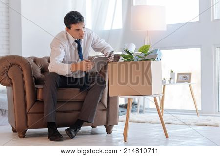 Reading. Attentive concentrated jobless man sitting in a brown armchair and reading old notes in a notebook while a box with personal things standing on a chair by his side