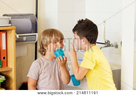 Two kids in classroom boys drinking water in school holding plastic glasses