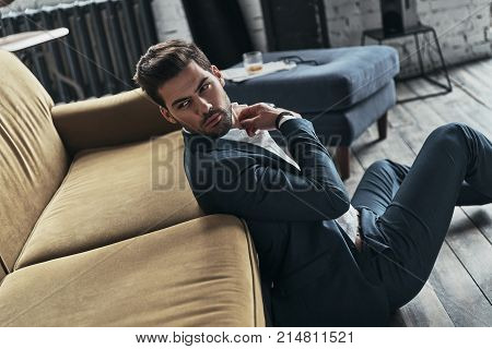 Impressive look. Handsome young man in full suit looking over his shoulder while sitting on the floor at home