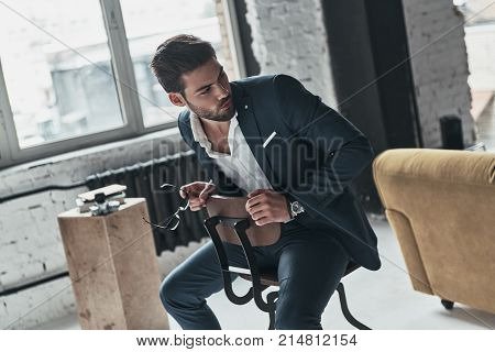 Confident young man. Handsome young man in full suit looking away while sitting on the stool