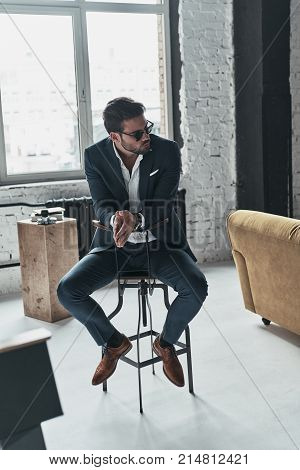 Handsome thinker. Good looking young man in full suit and eyewear keeping hands clasped while sitting on the stool