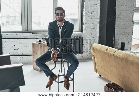 He got style. Handsome young man in full suit and eyewear keeping hands clasped while sitting on the stool