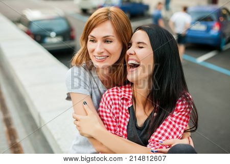 Two young sisters hugging, laughting and sitting near road in the street. one brunette girl in red plaid shirt, another redhead girl wearing gray shirt and blue skirt. concept of sincere friendship