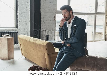 Thinking about something. Thoughtful young man in full suit looking away and keeping hand on chin while leaning on the sofa