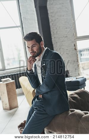 Thinking about something pleasant. Handsome young man in full suit smiling and keeping hand on chin while leaning on the sofa