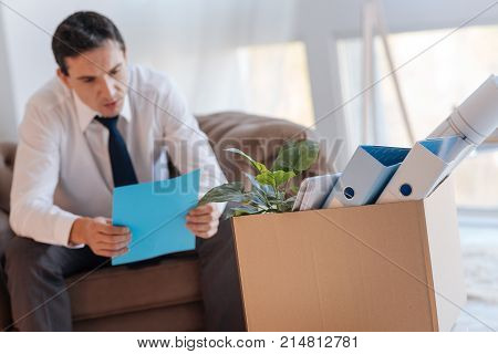 Important information. Concentrated calm young man sitting in an armchair and reading an important document after losing his job while a big box of personal things standing in front of him